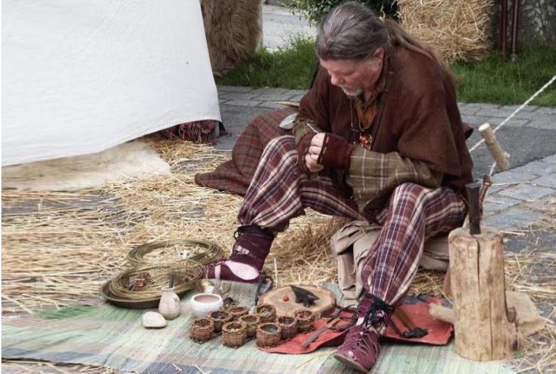 photo image d' une animation lors d' une fête gauloise organiser avec des artisans gaulois - Animation des vieux métiers d' artisan bourrelier et travail du cuir. Il réalise la fabrication des gallicae et calligae, type de chaussures sandales gauloise et romaine en cuir