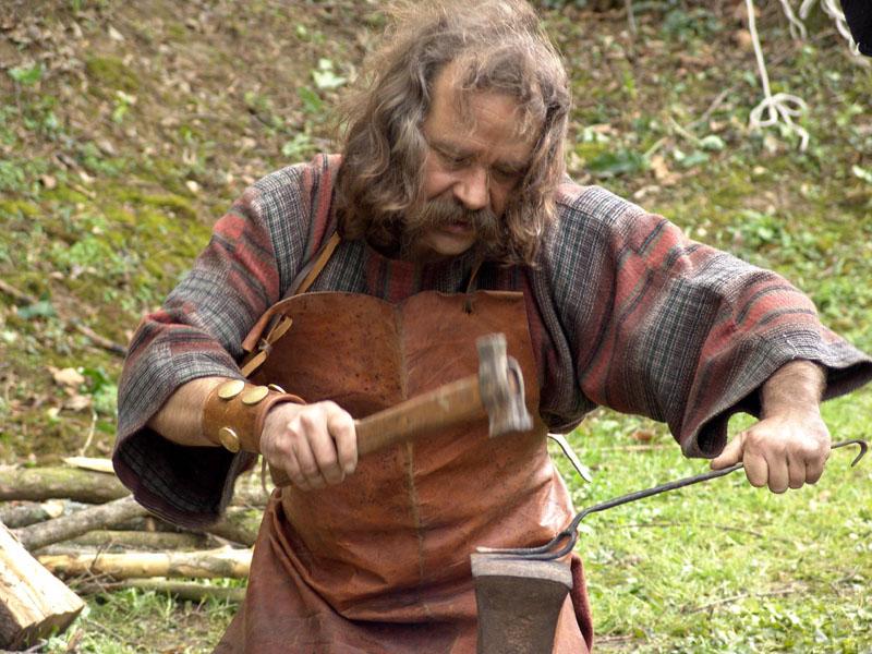 organisation et animation fete gauloise et celte - location reconstitution vieux métiers : artisan forgeron gaulois en costume à sa forge et son apprenti forgeron. Enclume et tas - soufflets de forge en cuir