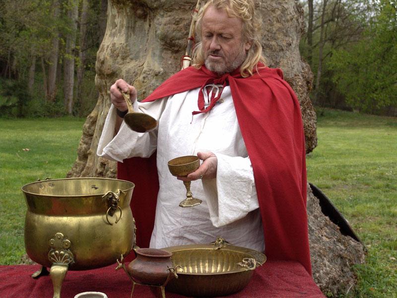Druide gaulois servant la libation traditionnelle lors de la sépulture d'un guerrier ou d' un prince celte. La vaisselle gauloise est en bronze, ornées de motifs animaliers divers. location Animation gauloise en costumes d' époque